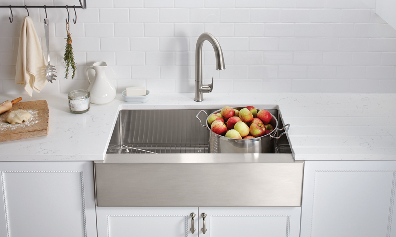 stainless steel under-mount sink, and a faucet, on a white countertop